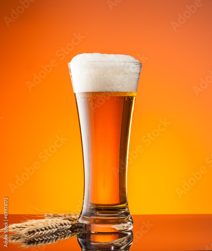 canvas print picture Glass of beer with orange background