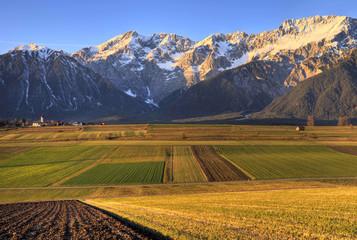 Felder mit Bergen im Spätherbst mit Schnee