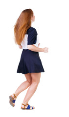 back view of running  woman in dress