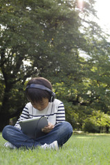 Boy that use the tablet it with headphones in the park