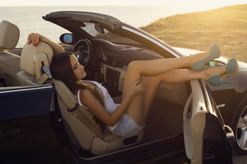 girl with dark hair posing in luxury cabriolet on sunset coast