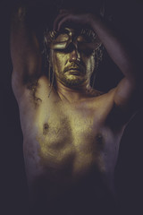painted golden bodypaint, man with gold helmet, ancient warrior