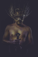 dramatic golden bodypaint, man with gold helmet, ancient warrior