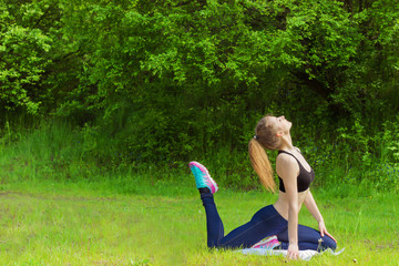 girl is engaged in sports yoga fitness on the beach by the rive