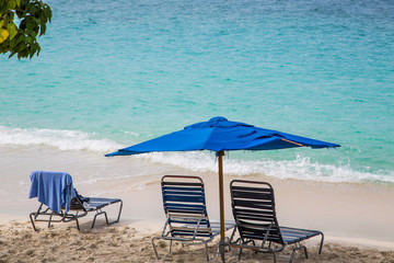 Chairs Under Blue Umbrella on Beach