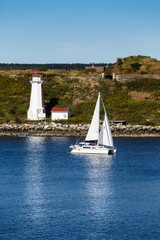White Sailboat Passing a White Lighthouse in Blue Water