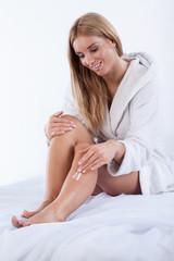 Sexy woman using body lotion