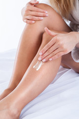 Applying body lotion on woman's legs
