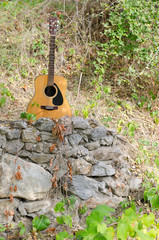 Acoustic guitar on a rock