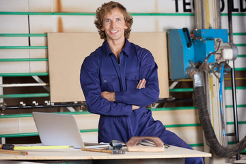 Confident Carpenter With Arms Crossed In Workshop