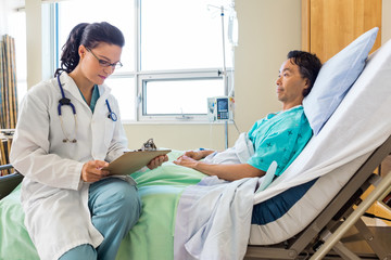 Doctor Holding Clipboard While Patient Looking At Her