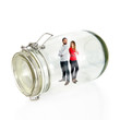 Couple inside glass jar over white background
