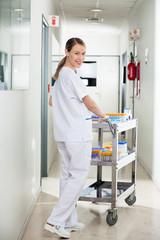 Technician Pushing Medical Cart In Hospital Hallway