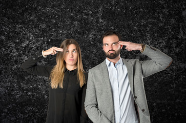 Couple making suicide gesture over black background
