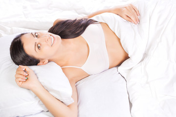 portrait of young beautiful woman in bed