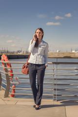 Frau steht im Hafen und telefoniert