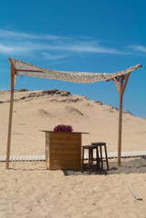 Wooden gazebo on the beach near the sand dunes