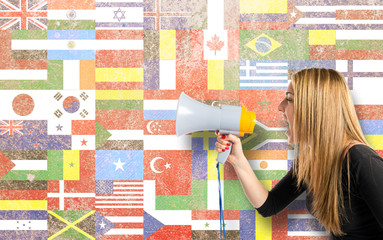 Pretty girl shouting with a megaphone over flags background