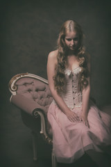 Vintage ballet fashion woman wearing pink corset and dress. Sitt