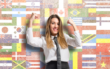 Young businesswoman winning over flags background