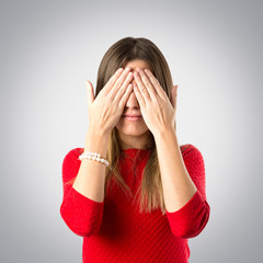 young girl covering her eyes over grey background