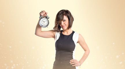 Pretty woman holding an antique clock over ocher background