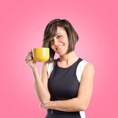 Pretty girl holding a cup of coffee over pink background