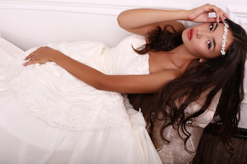 beautiful bride with dark hair in wedding dress posing at studio