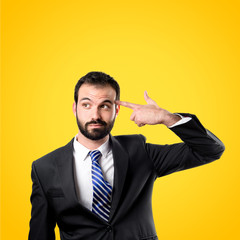 Young businessman committing suicide over yellow background
