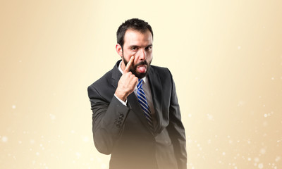 Young businessman making a mockery over ocher background
