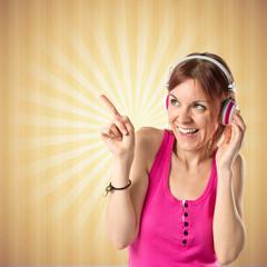 Young girl listening music over ocher background