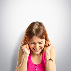 Young girl covering her ears over grey background