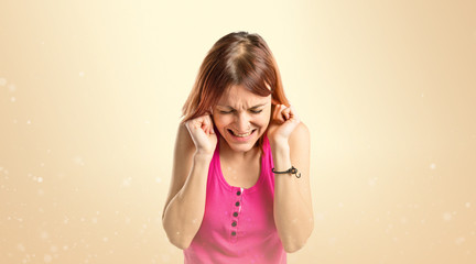 Young girl covering her ears over ocher background