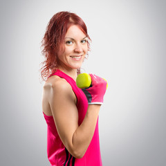 Redhead girl doing weightlifting over grey background,