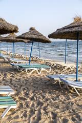 Sun umbrella on an empty beach and sea water horizon.