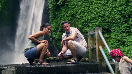 Happy family in front of beautiful waterfall, slow motion shot