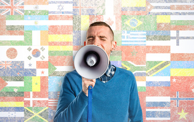 Redhead man shouting by megaphone over flags background