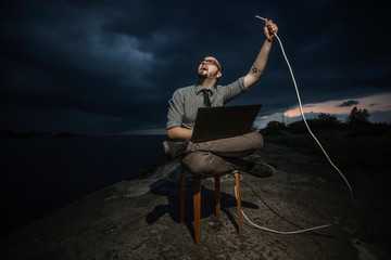 Man sits on a chair with laptop in outdoor with internet cable
