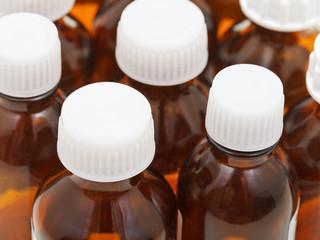 many little closed amber glass pharmacy bottles