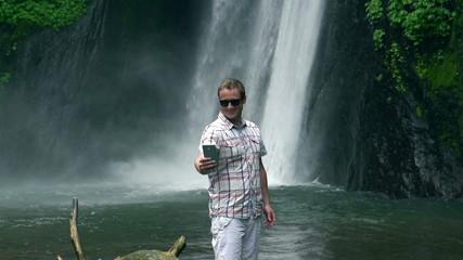 Happy man doing selfie against waterfall, slow motion 240fps
