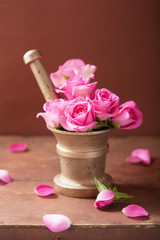 mortar with rose flowers for aromatherapy and spa