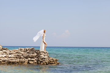beautiful bride stands on a cliff above the sea in glamorous