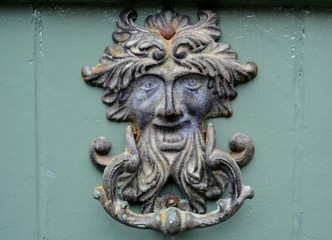 Old metal door knocker  with face
