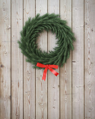 garland wreath with red ribbon on vintage wooden planks wall