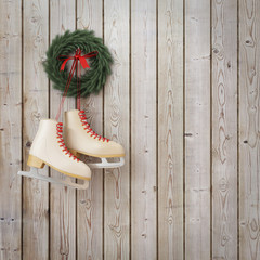 skates hanging on the wooden planks wall with garland