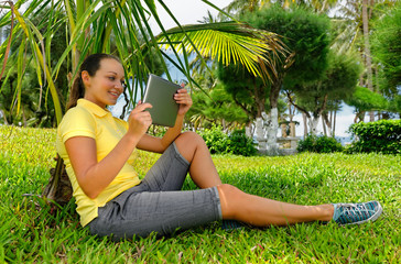 Side view of young woman on the lawn with her tablet computer