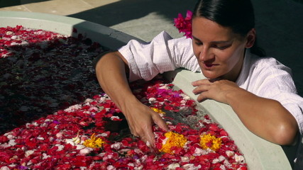 Happy woman touching flowers in the spa, slow motion 240fps