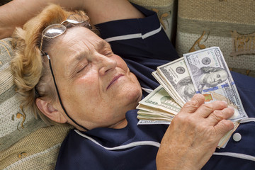 Woman pensioner sleeping with money in her hand