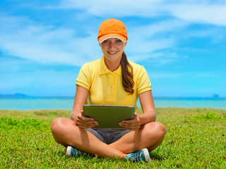 Beautiful young woman on the lawn with her tablet computer