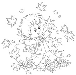 Joyful schoolboy throws up autumnal leaves